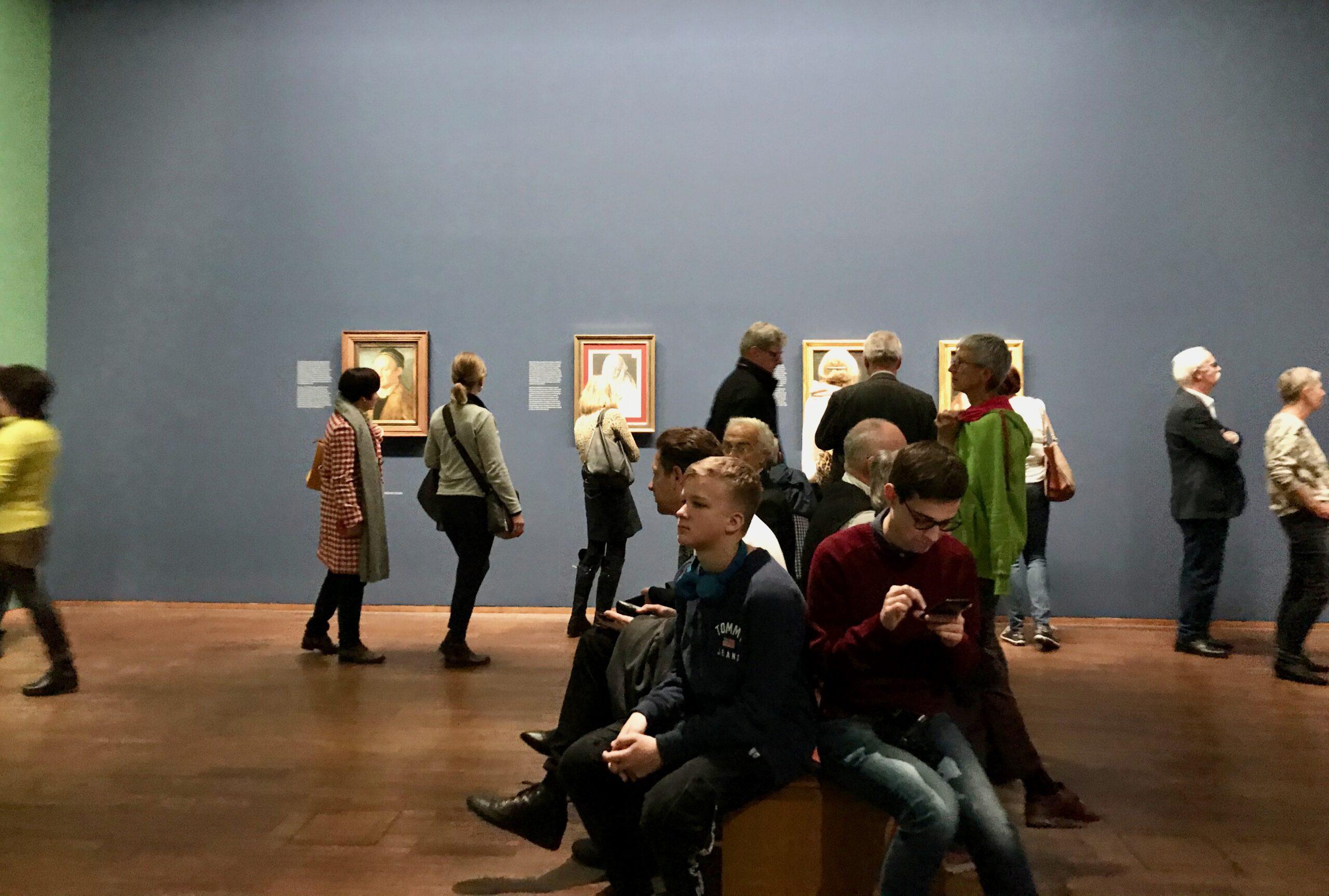 Na imagem vê-se uma sala de museu com visitantes