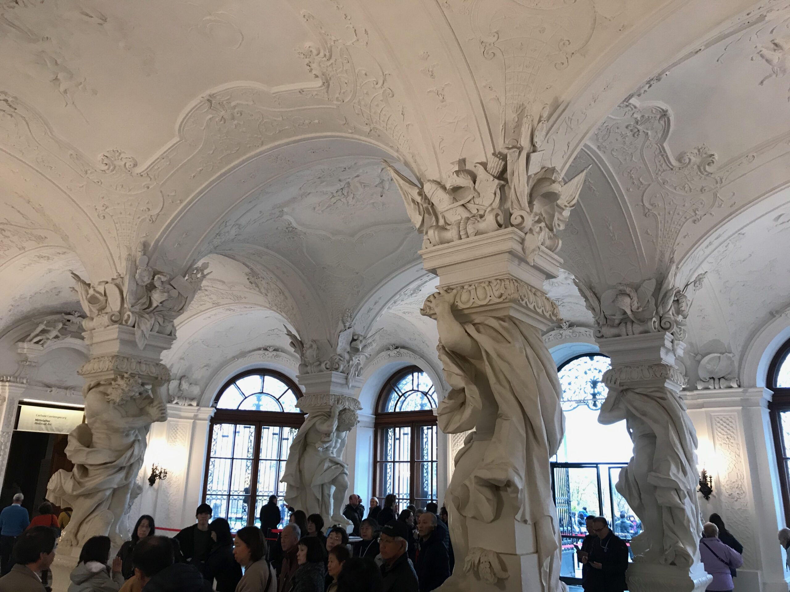 A imagem é o hall de entrada de um museu suportado por pesadas colunas decoradas