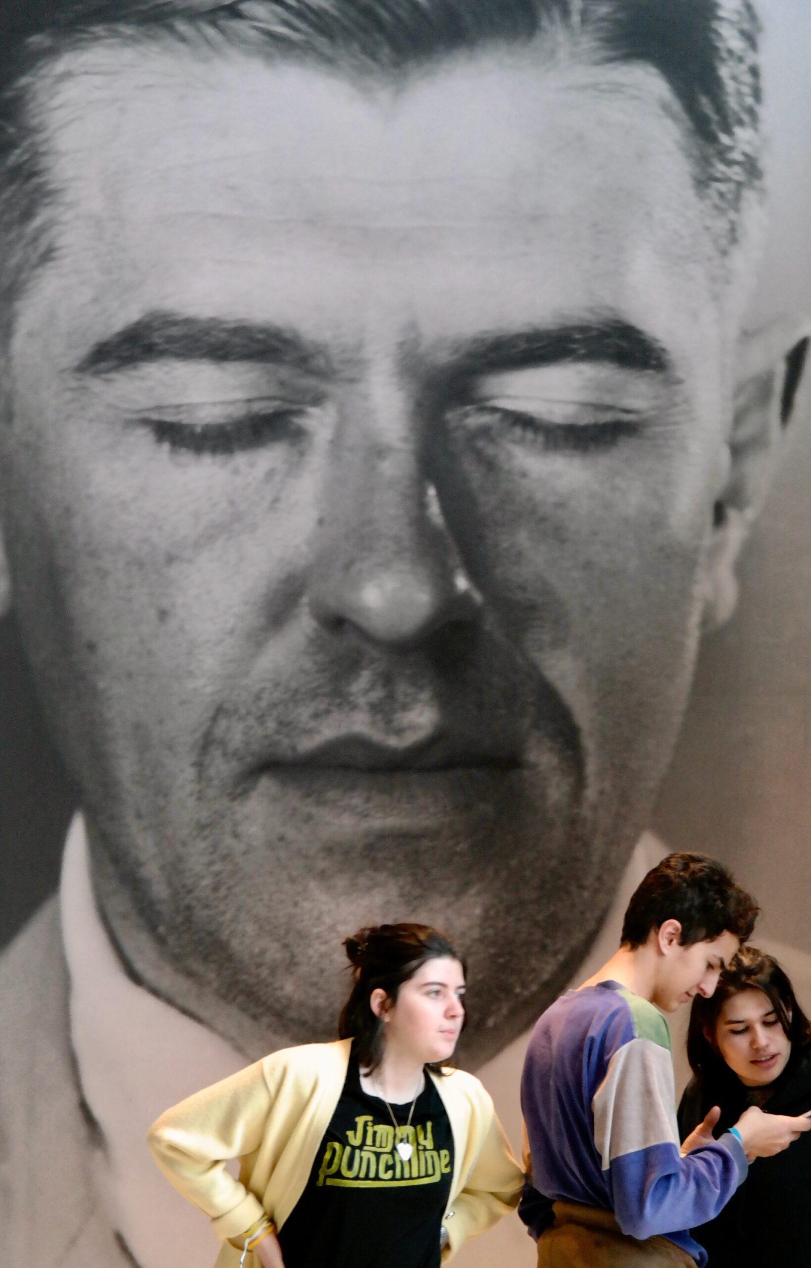 na imagem vê-se uma cena de museu, três jovens a olhar para um telemóvel e no fundo uma imagem a preto e branco de um homem de olhos fechados